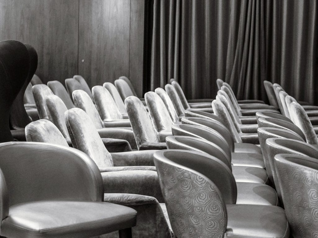 A black and white photo shows empty chairs gathered together in a ballroom on the ship.