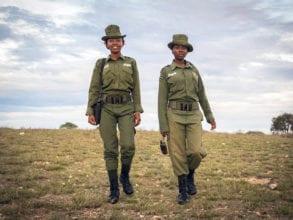 Two female Kenyan rangers dressed in green uniforms walk through the Kenyan wilderness.