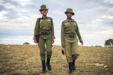 Two female Kenyan rangers dressed in green uniforms walk through the Kenyan wilderness.