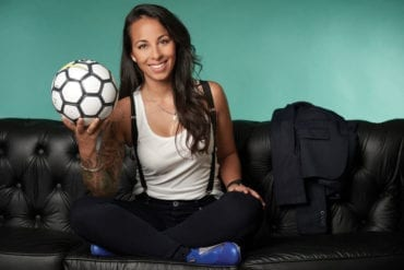 Evelina Cabrera, sits in a portrait with a soccer ball.