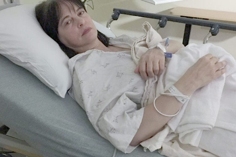A woman dressed in a white hospital gown is in bed waiting for surgery.