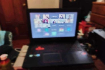 A black gaming laptop shows a zoom call.