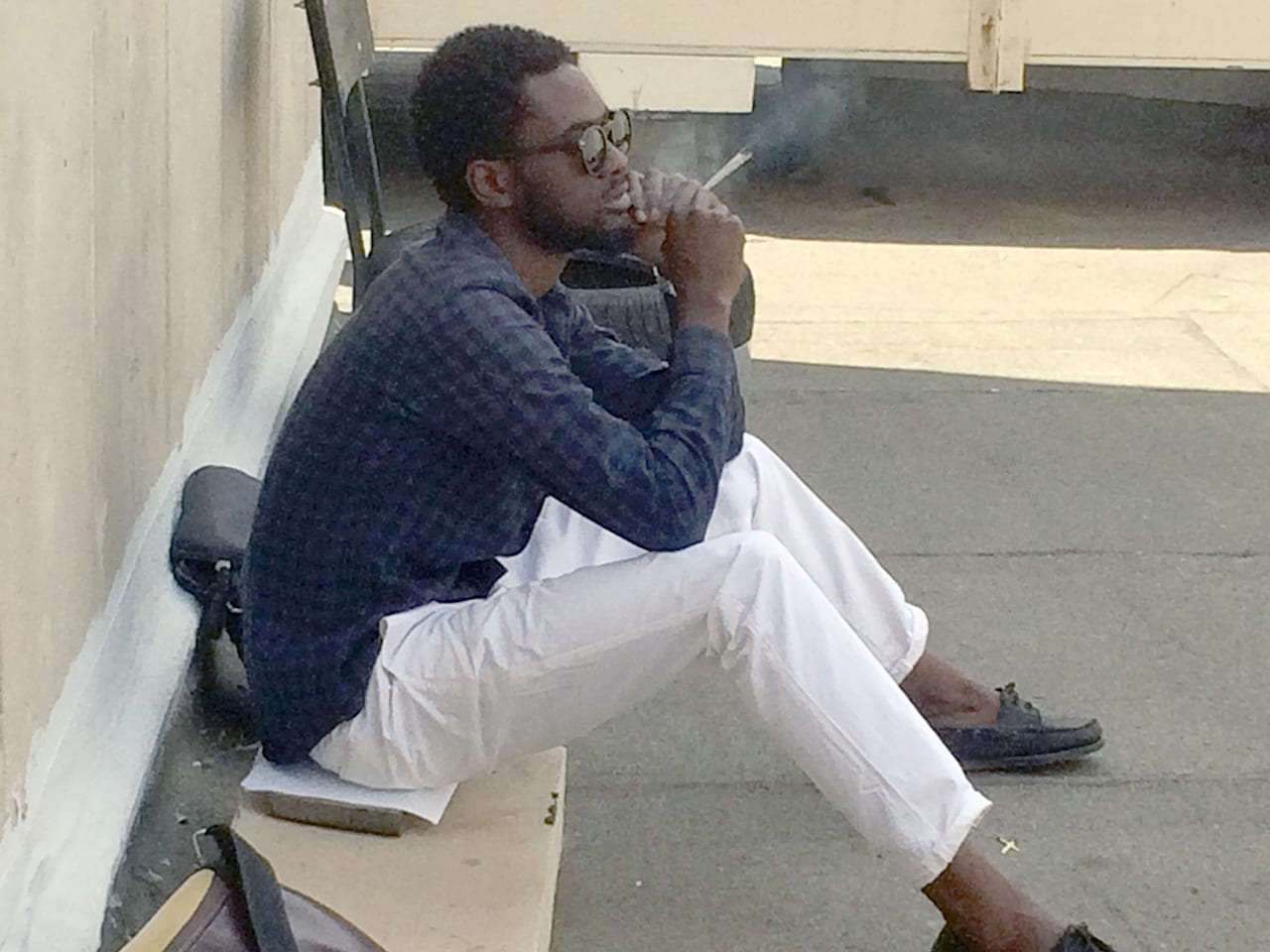 A young man wearing a blue shirt and white pants smokes a joint on campus.