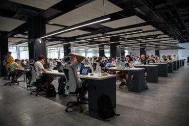 Una ilustración fotográfica que muestra a los trabajadores sentados en los escritorios.
