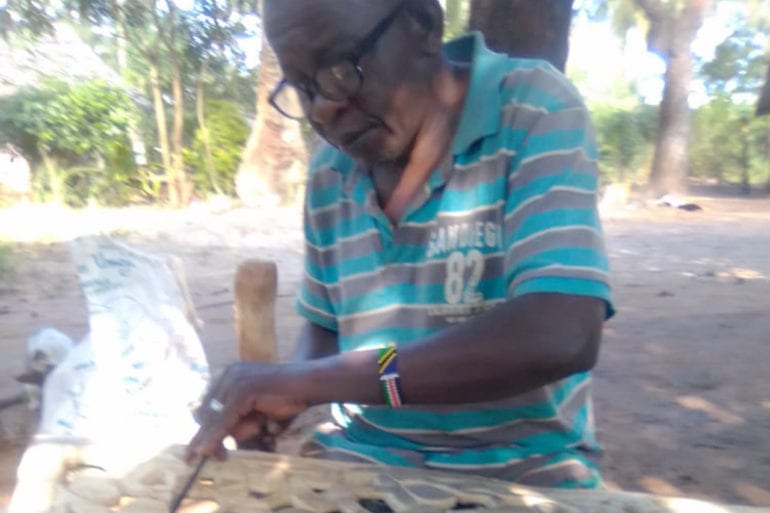 Thomas Nguli working on a sculpture.