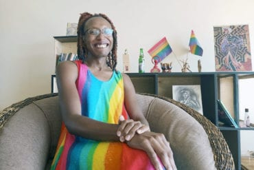 Arya Jeipea Karijo wears a rainbow dress in her living room while sitting with her arms crossed.