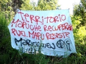 A protest sign made out of a white bed sheet.