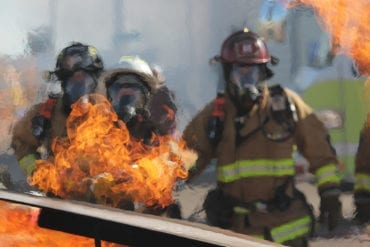 Firefighters stand before a blaze in this stock photograph.