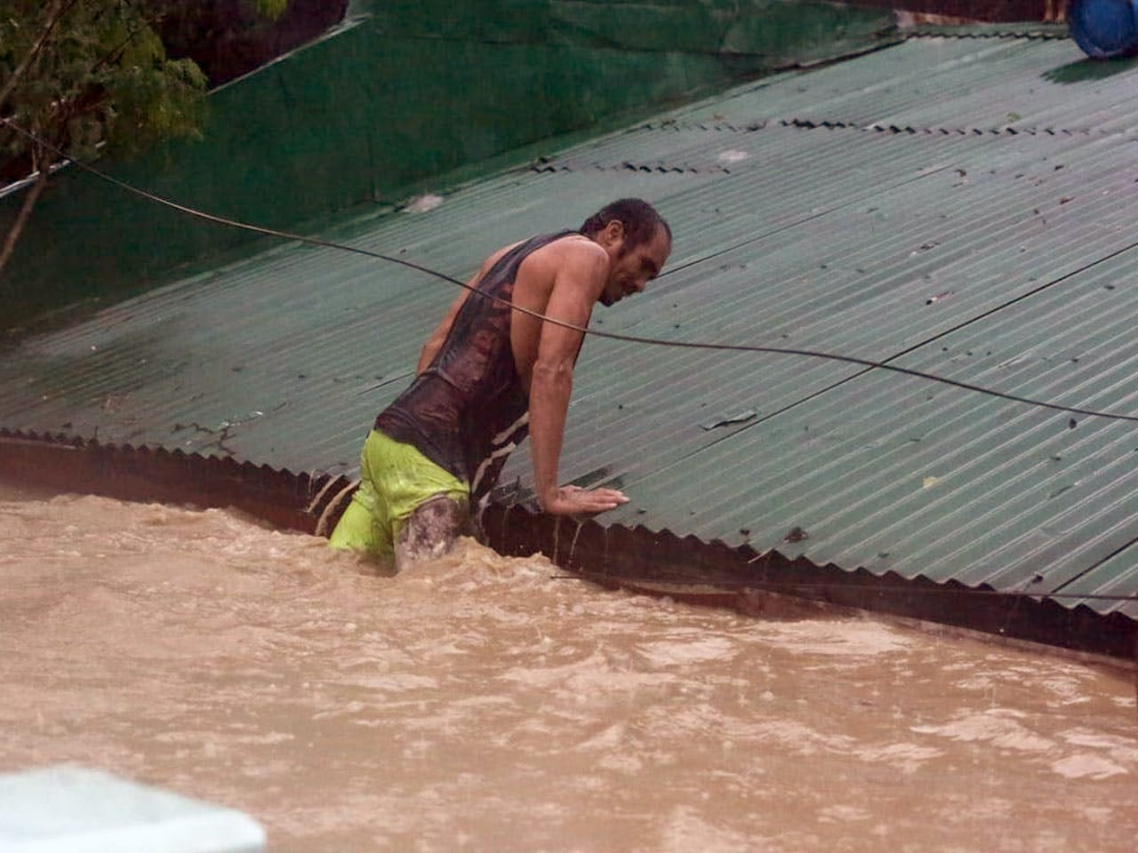 A man lifts himself onto a roof as his legs are submerged in flood water.