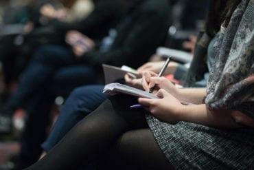 A photo illustration of a journalist taking notes.